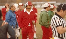 Joe Sanfilippo, wearing the headset. At left in blue jacket is his brother Sam. At right, over the official's shoulder, is Wally Huckno. Photo from 1982.