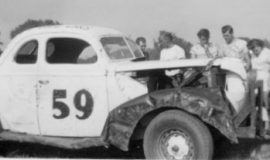 Lloyd Moore, second,from left, near the windshield, wearing a t-shirt, with his head turned. Julian Buesink is in front of the car adjusting the tow bar. Dunkirk, NY, 1950.