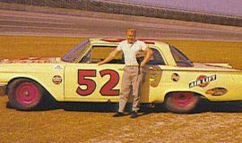Cale Yarborough standing beside Julian Buesink's 1961 Ford at Daytona in 1962.