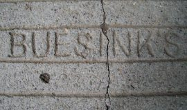 "Stone step that leads to office is inscribed ""Buesink's""."