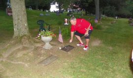 Joe DiMaio lays a flower at Bill Present's gravesite.