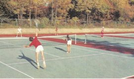 Photograph of several players on tennis court under tutelage of Nelson Turnell.