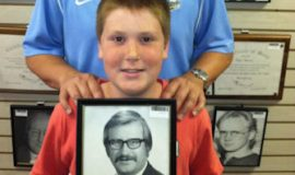 Chris Olsen and his son Ted posing at the CSHOF June 2014 with a photo of Ted's grandfather and namesake,Ted Olsen.