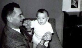Ted Sr. holding Ted Jr. - daughter Barbara in photo on table, 1961.