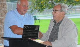 Town of Ellery supervisor Arden Johnson, right, presents a plaque to Tom Brown, son of the late Walt Brown. October 2018.