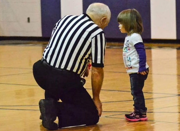 Basketball referree Paul Cooley shown down on a knee listening to small young girl on the court.