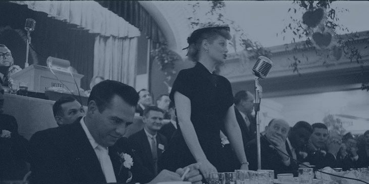 Lucille Ball stands at a microphone addressing the crowd at a 1956 Temple Hessed Abraham Sports Dinner. Seated beside her is her husband Desi Arnaz.