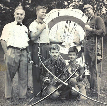 Louis Collins, a CSHOF inductee is standing with 4 boys and men, who are holding bows, by an archery target.,