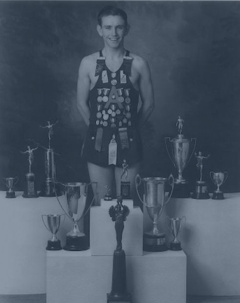 Brad Rendell standing with a collection of trophies and awards he earned.