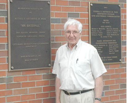 Russell Diethrick Jr. stands beside the plaque that bears his name.