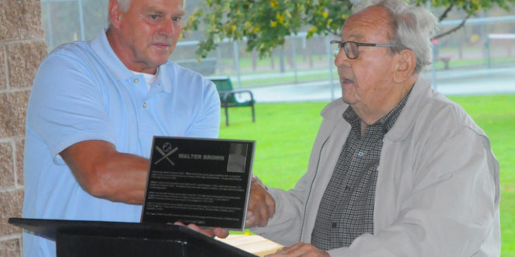 Town of Ellery supervisor Arden Johnson, right, presents a plaque to Tom Brown, son of the late Walt Brown, on Saturday. The town is dedicating a Little League field in the name of Walt, a Bemus Point native and former major league pitcher.
