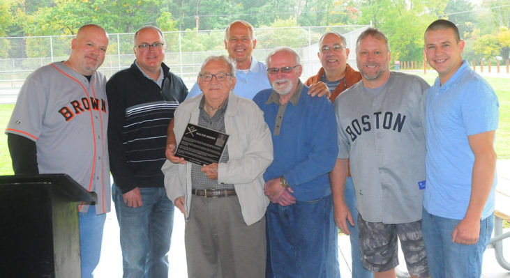 Joining in the dedication of the Little League field in Walt Brown's name are, from the left, Bradley Brown, grandson; Kris Brown, grandson; Arden Johnson, Town of Ellery supervisor; Tom Brown, son; Barry Brown, son; John Cresanti, Town of Ellery council member; Doug Brown, grandson; and Andy Brown, grandson.
