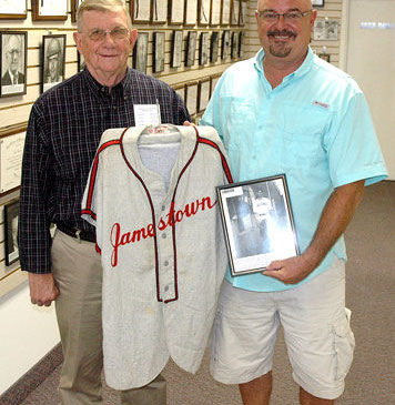 Chautauqua Sports Hall of Fame board member Russ Ecklund, left, accepts from Ted Wyberanec a jersey his father wore as a member of the Jamestown Merchants.