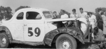 Dunkirk, NY, 1950. Lloyd Moore, second,from left, near the windshield, wearing a t-shirt, with his head turned. Julian Buesink is in front of the car adjusting the tow bar.