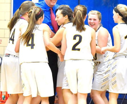 Mel Swanson is surrounded by his players after the Lady Wildcats' victory over Maple Grove.