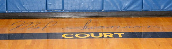 """Mel Swanson Court"" is painted on floor of gymnasium."