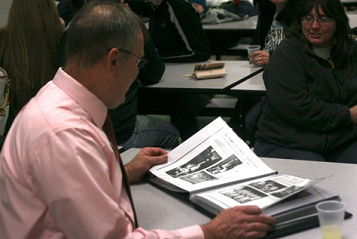 Sherman coach Mel Swanson flips through a scrapbook.