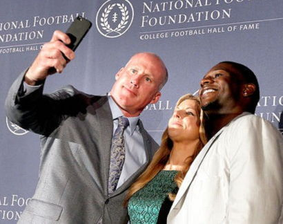Shane Conlan, left, and former TCU tailback LaDainian Tomlinson, right, pose for a selfie with event emcee Bonnie Bernstein.