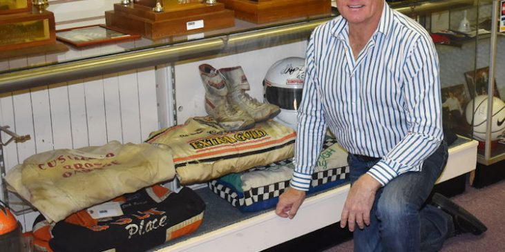 Dick Barton poses in front of memorabilia.