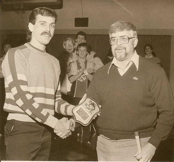 Sam Ognibene presents a commemorative plaque to Falconer wrestling coach Bill Davenport.