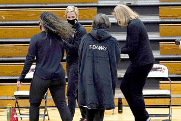 "Stanford coach Tara VanDerveer, center, wears an overcoat with ""T-DAWG"" on the back."